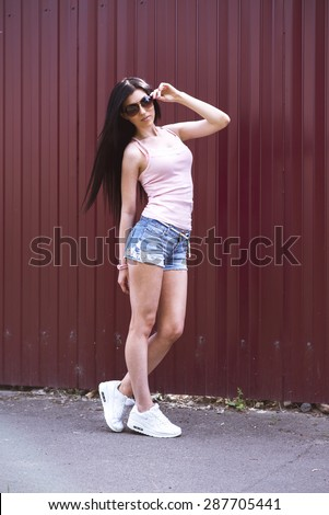 Beautiful young girl in glasses shorts pink blouse, posing on the street, fashion style glamor girl standing in front of a brown fence holding glasses - stock photo