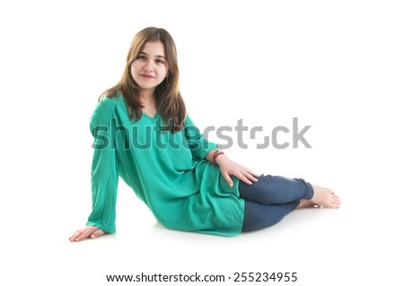Beautiful young girl in green tunic sitting on the floor isolated on white background - stock photo