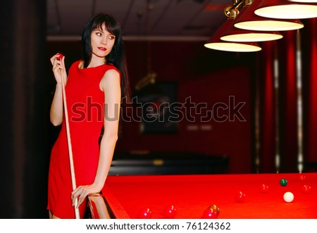 Beautiful young girl in red dress playing a billiards.