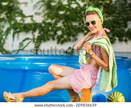 Beautiful young girl in retro look with red lips in retro swimsuit, a headscarf and sunglasses happy smiling with swimming pool in the background. copy space - stock photo