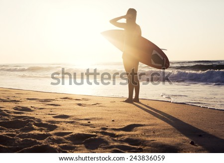 Beautiful young girl in the beach with her surfboard