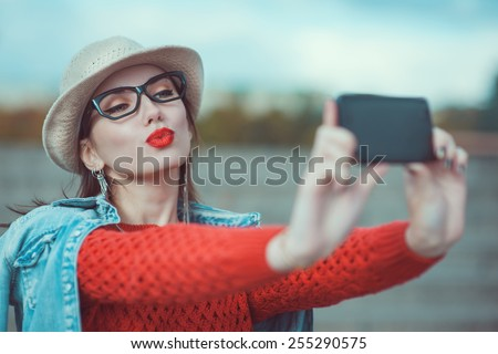 Beautiful young girl in the hat taking picture of herself, selfie outdoor - stock photo