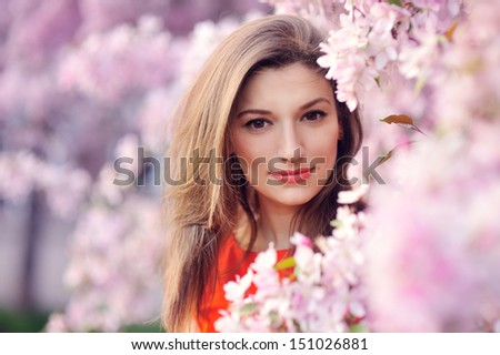Beautiful young girl in the park and a flowering tree - stock photo