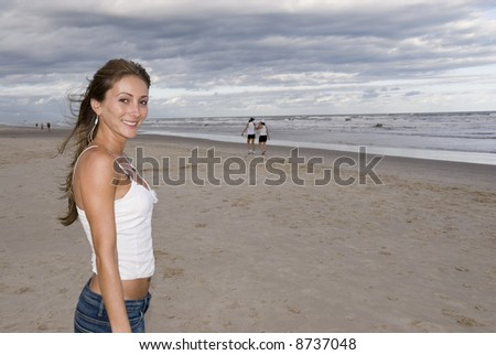 Beautiful young girl in the sand (late afternoon), with cloudy sky. - stock photo