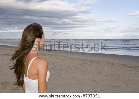 Beautiful young girl in the sand (late afternoon), with cloudy sky, looking out into the sea. - stock photo