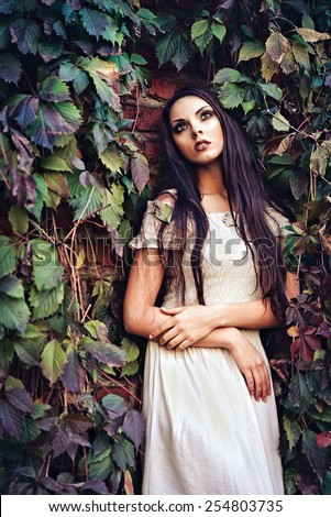 Beautiful young girl in white dress standing among colorful leaves - stock photo