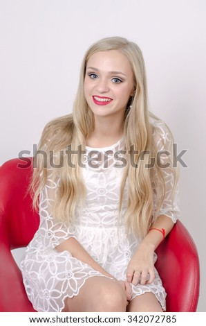 Beautiful young girl in white short dress sitting on modern red chair, high heels, professional make-up. smile. happy