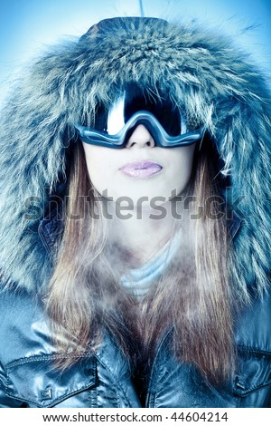Beautiful young girl in winter clothes and dressed in fur hood  and snowboard goggles. - stock photo