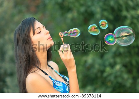 beautiful young girl inflating colorful soap bubbles in nature