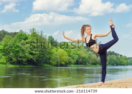beautiful young girl is engaged in sports, yoga, fitness on the beach by the river on a Sunny summer day - stock photo