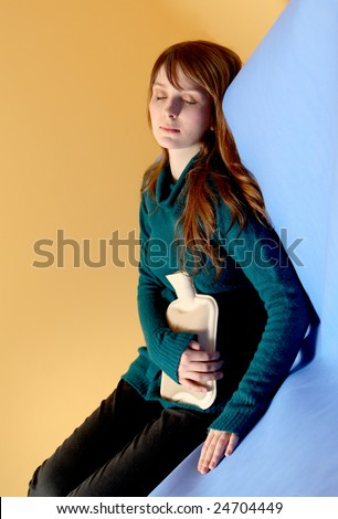 Beautiful young girl is laying on the bed with hot bottle water and relaxing. - stock photo