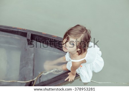 Beautiful young girl is looking on you from the sinking boat. Focus point on the face. - stock photo