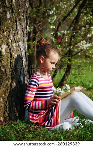 beautiful young girl is reading book in the park, sitting on the grass near the tree - stock photo