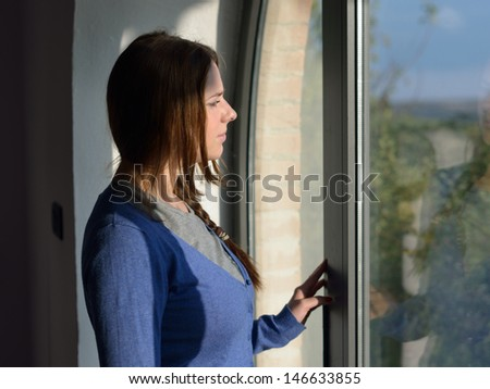 Beautiful young girl is waiting near window looks trough glass. Bright sunlight