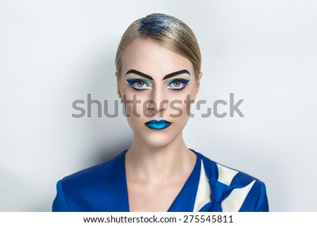 Beautiful young girl, lady, actress, model, character. Bold creative look, fashion style. Ideal expressive makeup, bright blue black lips, eye brows, arrows, design art ultramarine white business suit - stock photo