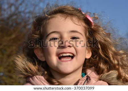 Beautiful young girl laughing. She is wearing a coat with a furry collar. - stock photo