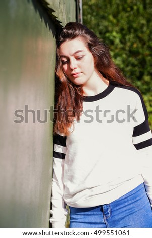 Beautiful young girl leaning on a railing whilst casually looking at the camera