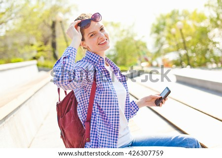 Beautiful young girl looking at camera with cell phone in one hand holding her glasses with another in park on sidewalk. Relaxing in hot and sunny summer day after phone talk. Casual look. Copy space - stock photo