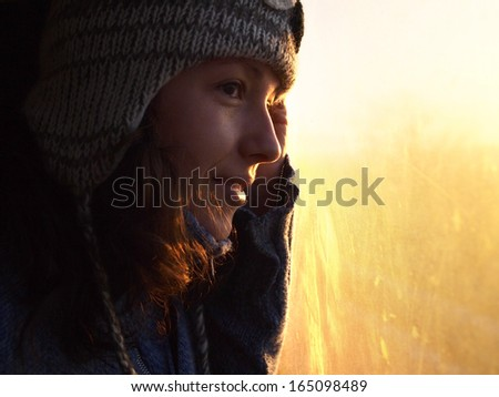 Beautiful young girl looking through the window towards the golden morning light - stock photo