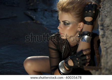 beautiful young girl looks like a rock star sits on a background of water
