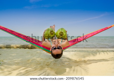 Beautiful young girl lying in a hammock holding two coconuts with sea on the background - stock photo