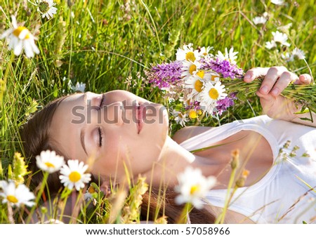 beautiful young girl lying in a marguerite meadow - stock photo