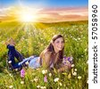 beautiful young girl lying in a sunset marguerite meadow - stock photo