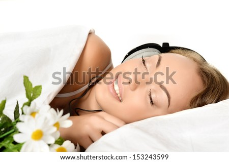 Beautiful young girl lying in bed with flowers bouquet and listening music