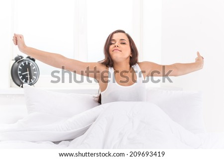 Beautiful young girl lying in bed. Young beautiful, woman waking up fully rested.  - stock photo