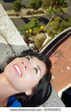 Beautiful young girl lying on building roof with the city in the background - stock photo
