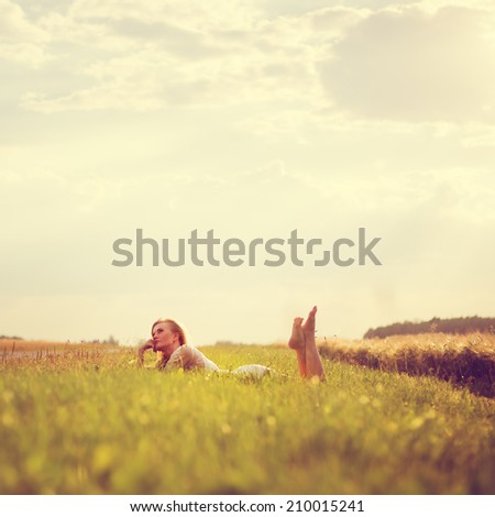 Beautiful young girl lying on the field - stock photo