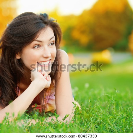 Beautiful young girl lying on the grass on a background of green nature - stock photo