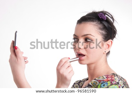 Beautiful young girl making up her lips with lipstick - stock photo