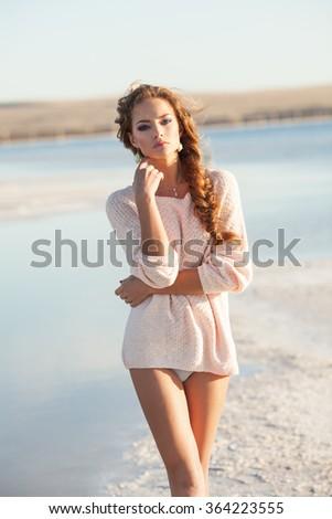 Beautiful young girl near a lake - stock photo