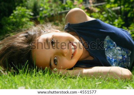 Beautiful young girl of mix ethnicity having fun laying in the sunshine - stock photo