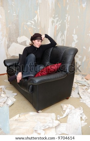 Beautiful young girl on a sofa in the empty room - stock photo