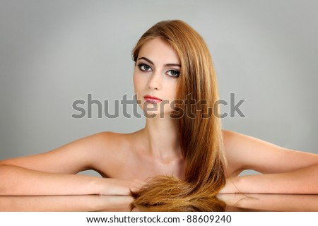 Beautiful young girl on gray background - stock photo