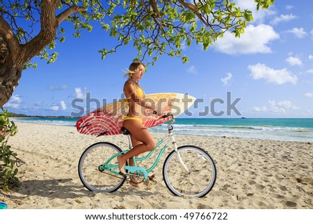 beautiful young girl on her bicycle with surfboard at kailua beach, hawaii - stock photo