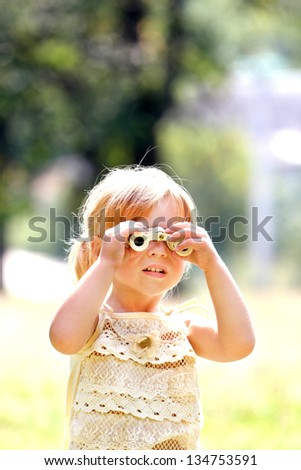 beautiful young girl on nature with binoculars - stock photo