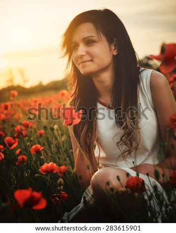 Beautiful young girl on poppy field with dress