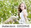 Beautiful young girl on summer flowers field - stock photo