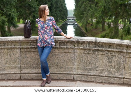 Beautiful young girl on the old stone bridge in the coniferous forest - stock photo