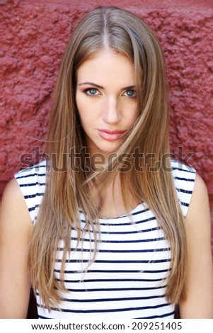 Beautiful young girl on wall background, outdoors - stock photo