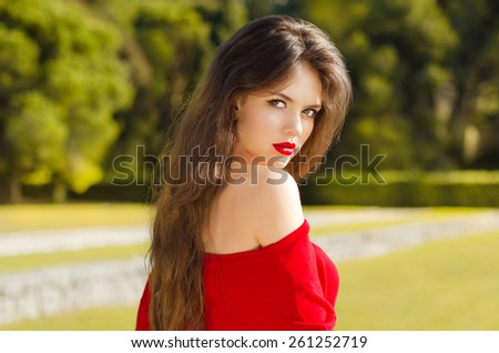 Beautiful young girl Outdoor portrait. Attractive Woman with red lips posing. Romantic model resting in green park. - stock photo