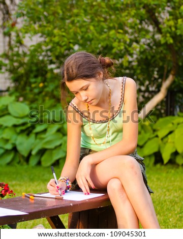 Beautiful young girl painting in the park, sitting on the bench - stock photo
