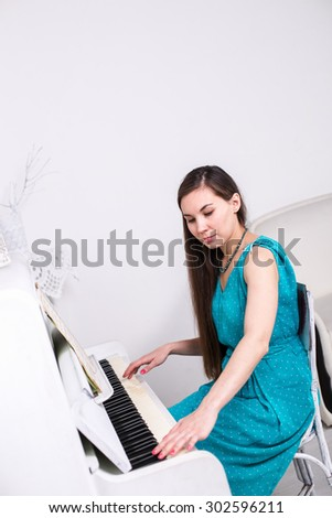 Beautiful young girl playing on a white piano - stock photo