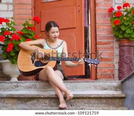 Beautiful young girl playing the guitar outdoors - stock photo