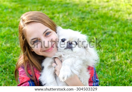 beautiful young girl playing with her dog outdoor  - stock photo