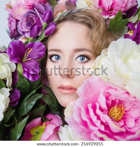 Beautiful young girl portrait in spring colorful flowers