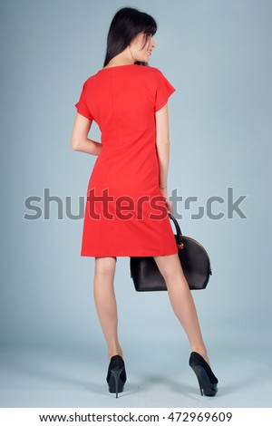 Beautiful young girl posing in street clothes on blue background.Isolated studio portrait.Back View Portrait
